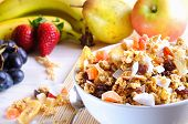 stock photo of fruit bowl  - Bowl of cereal with fruit on a white wooden table and fresh fruits behind closeup - JPG
