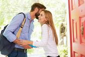 stock photo of leaving  - Woman Saying Goodbye To Man Leaving Home With Packed Lunch - JPG