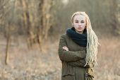 image of dread head  - Young beautiful blonde hipster woman in scarf and parka with dreadlocks hairstyle posing on a blurry forest background - JPG