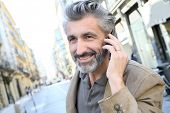 stock photo of people talking phone  - Mature man talking on the phone in the street - JPG