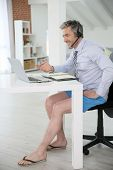 stock photo of stressless  - Businessman on video meeting from home in relaxed outfit - JPG