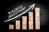 picture of ascending  - Words Business Investment on ascending arrow above bar graph of Wooden small cubes isolated on black background - JPG