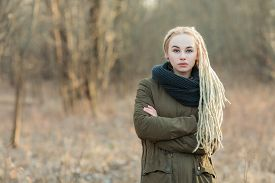 stock photo of dreadlock  - Young beautiful blonde hipster woman in scarf and parka with dreadlocks hairstyle posing on a blurry forest background - JPG