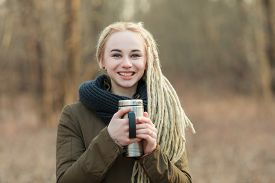 foto of thermos  - Young laughing beautiful blonde hipster woman in scarf and parka with dreadlocks hairstyle posing on a blurry forest background with a thermos cup - JPG