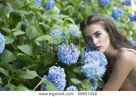 Portrait Of Pretty Woman And Blue Flowers