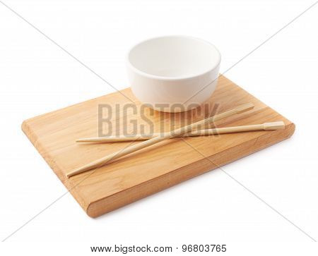 Ceramic bowl and chopsticks over the board