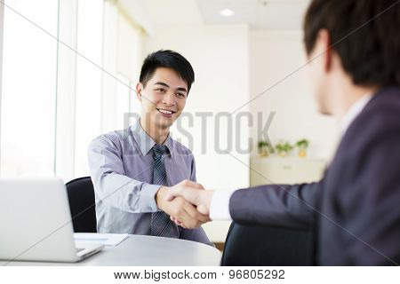 happy business man hand shaking in office
