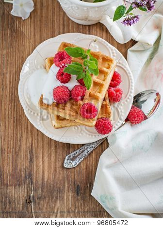 Crispy wafers with cream and fresh raspberries for breakfast