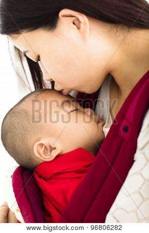 Mother Kissing  Baby In A Baby Carrier