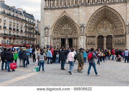Tourists Visiting The Notre Dame Cathedral In Paris, France
