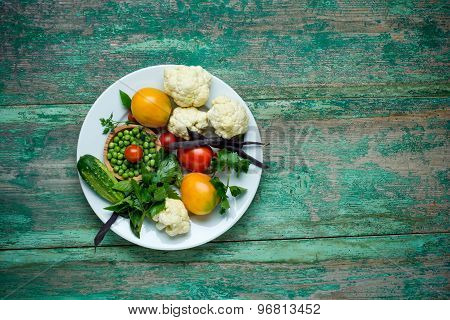 Vegetables . Fresh Bio Vegetable on a plate. Over wooden background