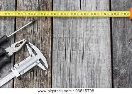 Different Construction Equipment On A Wooden Background