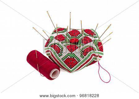 Pincushion (hand-made) with pins.