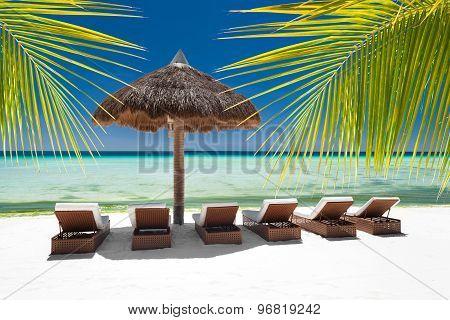 Sun Umbrella And Beach Beds On Tropical Coastline
