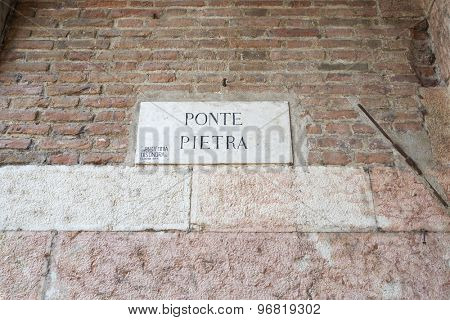 VERONA, ITALY - JULY 13: Street sign for Ponte Pietra on old brick wall. July 11, 2015 in Verona.