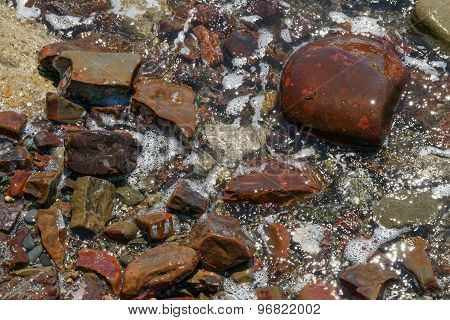 Close-up Of Wet Red Stones In Foam Bubbles As Background.