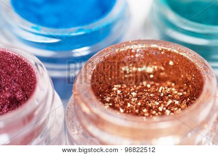 Close up of glass jars with metallic glossy eye shadows on white background