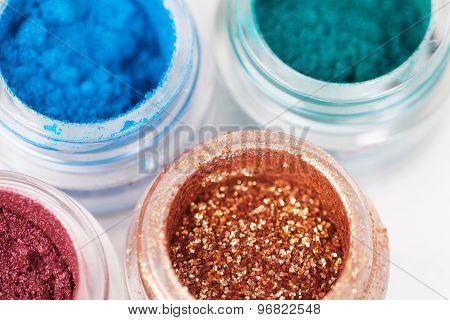 Set of four glass jars with metallic glossy eye shadows on white background