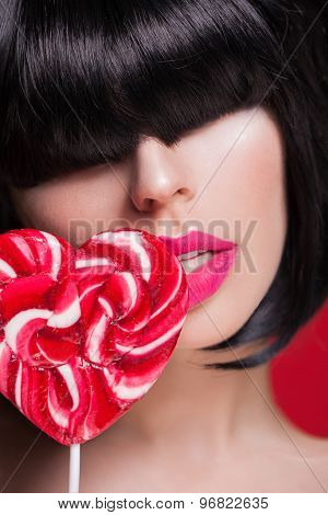 Closeup portrait of model with beautiful sexy pink big lips and lollipop on red
