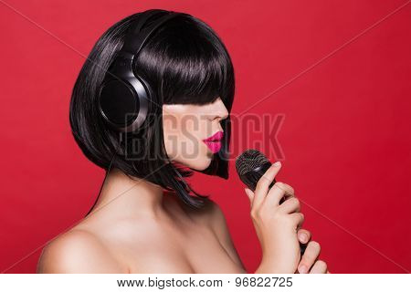 Stylish girl singing with a mike, red background