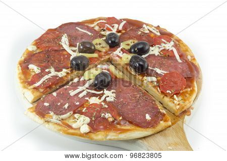 Sliced Round Pizza And Raw Vegetables Served On A Wooden Plate On White Background