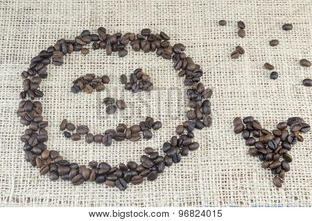 Smiley Face And Heart Shape  Made Entirely Out Of Coffee Grains Placed On Coffee Bag