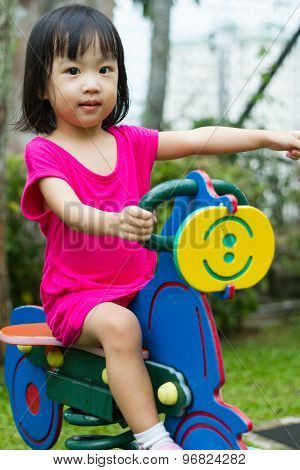 Asian Kid Riding At Park