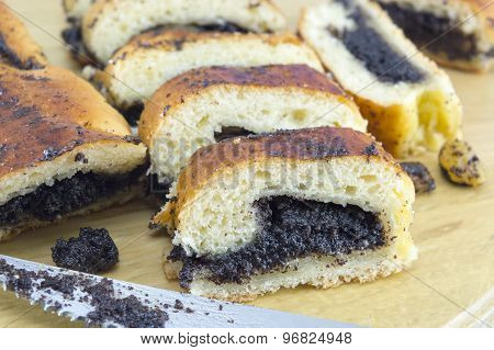 Homemade Poppy Seed Sliced Strudel  And A Knife On A Wooden Board