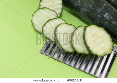Sliced And Whole Cucamber Ordered On Top Of The Chopper On Green Background