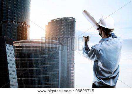 Builder Pointing At Skyscraper