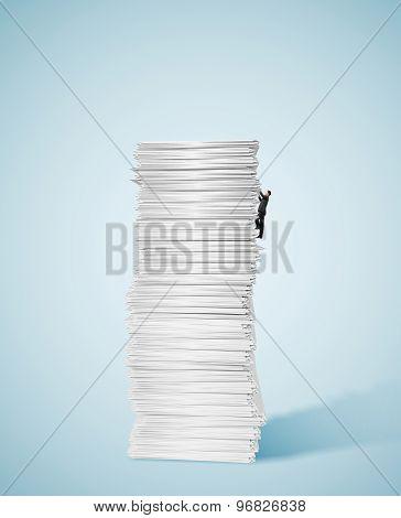 Businessman Climbing Up A Huge Big Stack Of Paper
