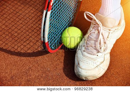 Legs of man near the tennis racquet and balls