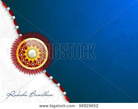 Beautiful glossy rakhi on shiny floral design decorated blue and white background for Indian festival, Raksha Bandhan celebration.