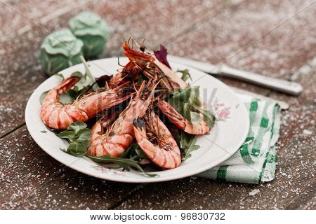 Grilled shrimps served outdoor in winter, snow on table, toned image
