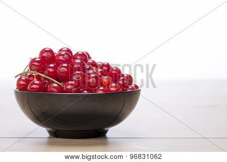 Black Bowl With Redcurrants On A Wood Table, White Background