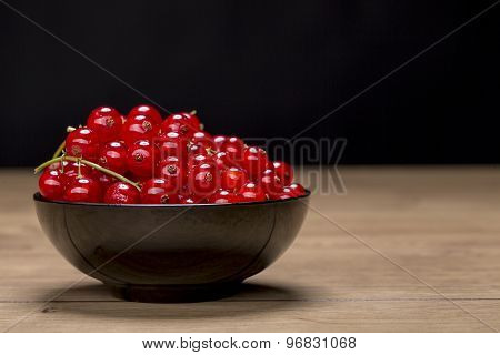 Black Bowl With Redcurrants On A Wood Table, Black Background