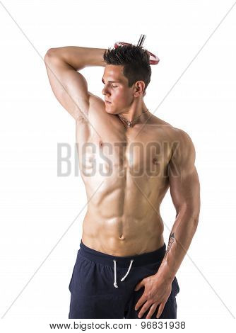 Muscular shirtless young man exercising triceps with dumbbells