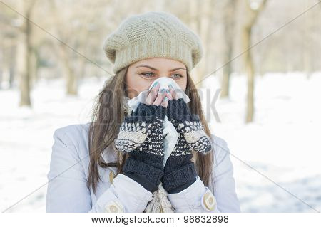 Young Woman In Winter Clothing Blowing Nose