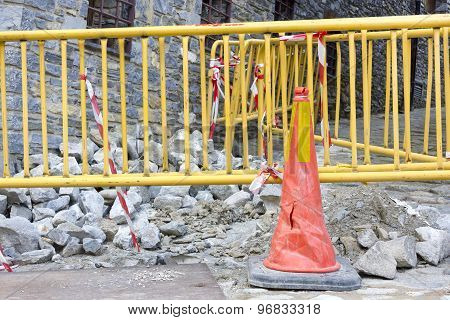 Red cone with yellow construction barriers