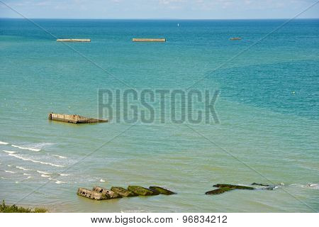 Ruins of harbor built by the Allies in Arromanches, Normandy, France.