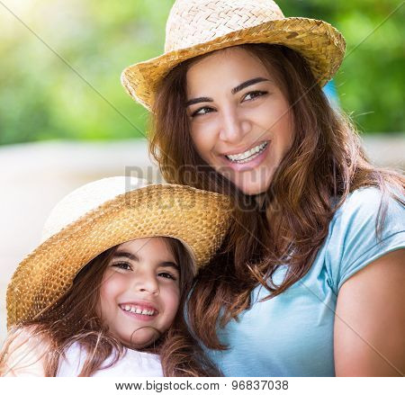 Portrait of happy family outdoors, cute cheerful mother with little daughter wearing identical straw hats and having fun on backyard
