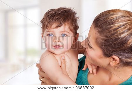 Portrait of happy young mother holding on hands cute little son and looking on him with great love, with pleasure spending time at home, enjoying motherhood