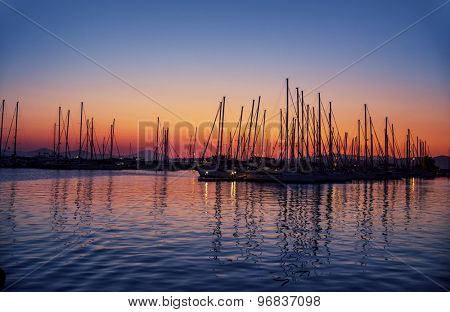 Harbor on sunset, silhouettes of luxury sailboat moored in the port in the evening, beautiful coastal view, active summer vacation