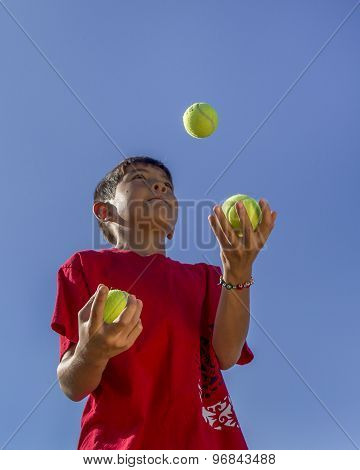 Boy Juggles Tennis Balls.