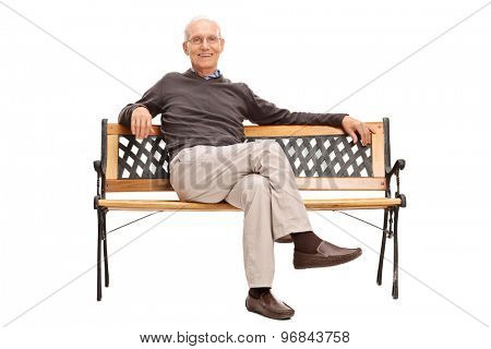 Studio shot of a serene senior sitting on a wooden bench and looking at the camera isolated on white background