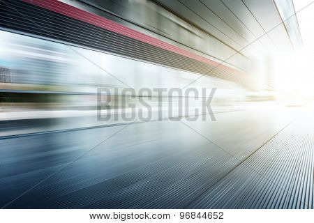 Blurred motion of modern building glass wall and empty path
