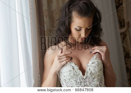 Fascinating bride looks at her decollete