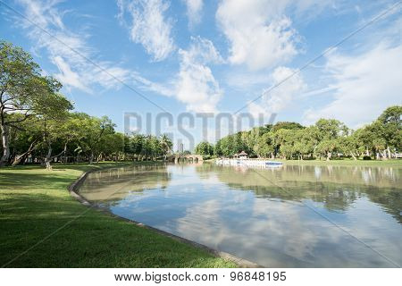 View Of Park With Lake, Blue Sky, Clouds And Green Leaves Of Trees