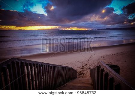 Otama Beach. Stairway Leading To The Sand Beach. Cloudy Sky At Sunset