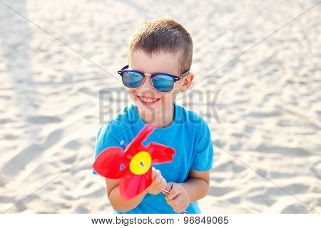 Little Boy With Pinwheel On Beach